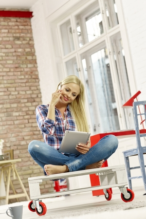 Attractive young woman sitting in retro home, talking on mobilephone using tablet computer. Stock Photo