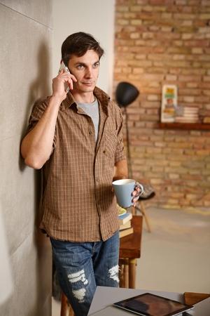 Casual man talking on mobilephone at home, holding tea mug.