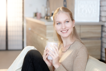 Beautiful nordic woman smiling happy at home, holding tea cup, looking away. Stock Photo
