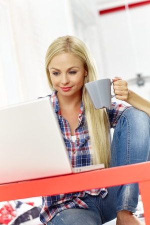 Young woman sitting at desk at home, using laptop, drinking tea. Stock Photo