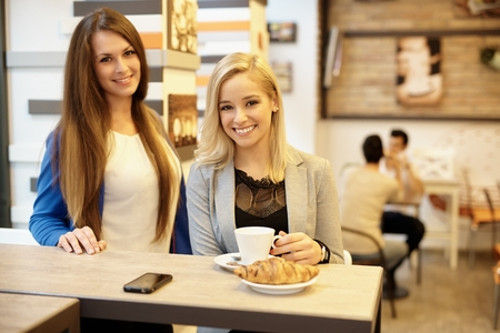 Portrait of happy girls having breakfast in cafeteria, smiling, looking at camera. Stock Photo