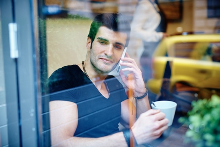 Young man sitting in cafeteria, drinking coffee and talking on phone. Photographed through window.