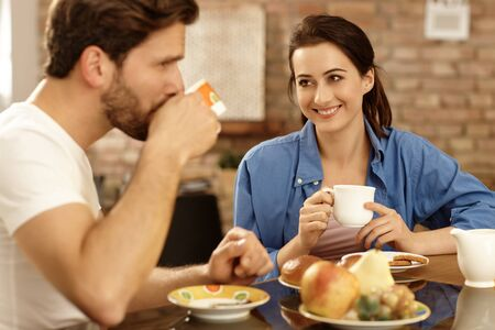 Loving couple having breakfast together at home, smiling happy. Stock Photo