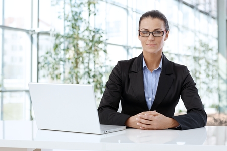 Professional businesswoman sitting at desk waiting to give business advice.