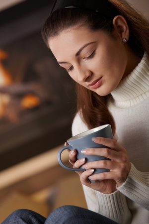 Young woman sitting at fireplace on a winter day, drinking hot tea, smiling. Stock Photo
