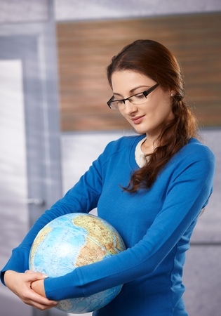 Portrait of young female student in glasses, holding globe, looking down, smiling. Stock Photo