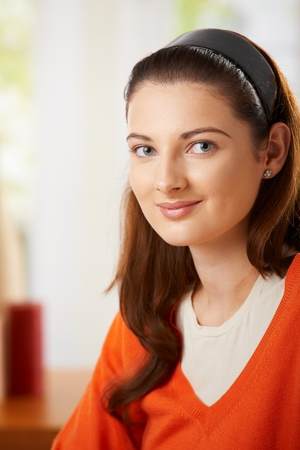 Portrait of teenage girl, looking at camera, smiling.