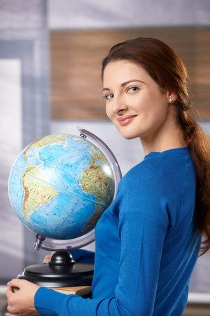 Female student walking on school corridor, carrying globe, looking at camera, smiling.