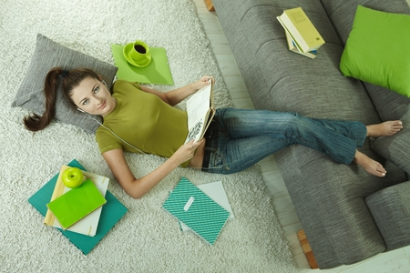Young woman lying on floor at home, studying. Looking at camera. Directly above view.