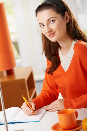 note booklet: Student girl sitting at desk at home studying writing to workbook, looking at camera smiling.