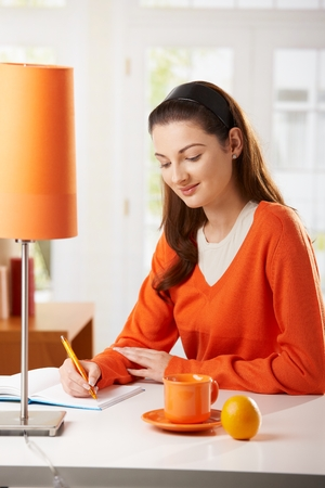 note booklet: Young woman sitting at desk at home, writing notes to diary, looking down, smiling. Stock Photo