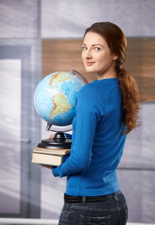 Happy female student standing on school corridor, holding globe, looking back over shoulder, smiling.