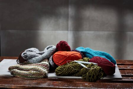 Colorful balls of wool and knitting needle on a wooden surface.