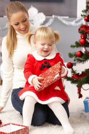 Little girl opening christmas present, sitting on mothers lap.