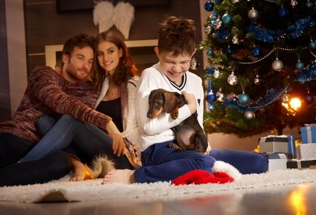 Glücklicher kleiner Junge, der den Welpen empfängt für Weihnachten, Eltern aufpasst vom Hintergrund hält% 00 Standard-Bild - 90439155
