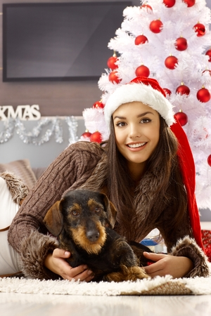 Pretty woman in santa hat smiling, hugging dog, lying on floor by christmas tree.