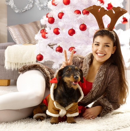 Beautiful young woman celebrating christmas with dog, smiling, looking at camera. Stock Photo