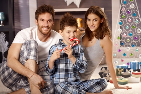 Attractive young family with little boy smiling happy at christmas morning, boy having lollipop.