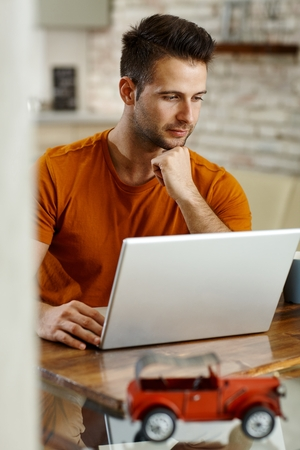 Young man working with laptop computer. Stock Photo