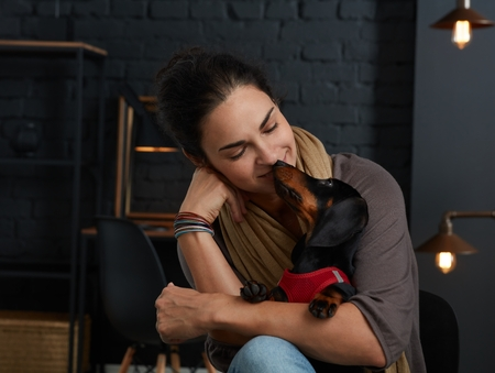 Mature woman with little dog in love at home.