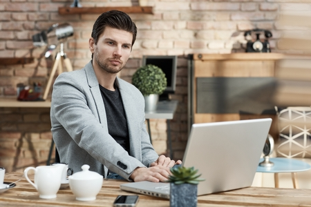 Young businessman sitting at table, using laptop.
