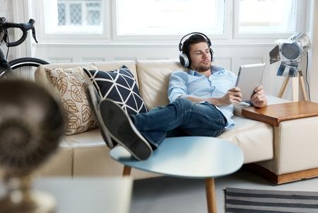 タブレットとヘッドフォンを使用するソファに横になっている若い男。