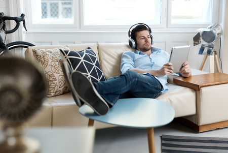 Young man lying on sofa, using tablet and headphones.