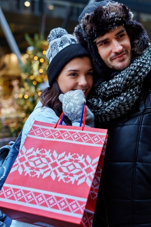 Young couple doing christmas shopping in the city, smiling, hugging.