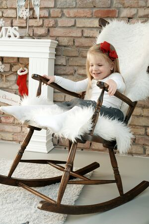 Adorable little girl enjoying swinging in rocking-chair at christmas time. Stock Photo