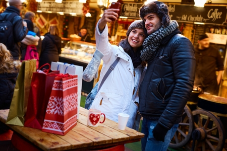 Happy young couple making selfie at christmas fair.