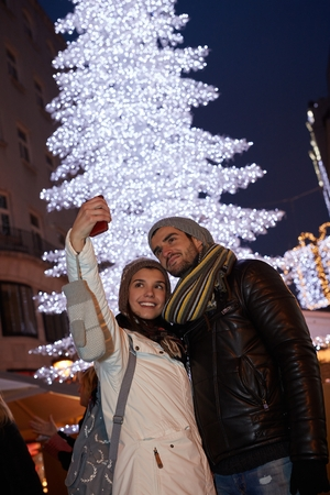 Happy young couple making selfie outdoors front of huge christmas tree.