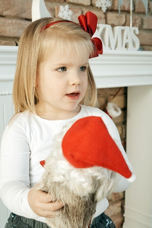 Sweet little girl celebrating christmas, holding santa claus in hand. Stock Photo