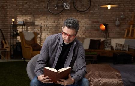Het oudere boek van de blanke mensenlezing thuis. Draag casual, grijs haar en een trendy rode bril.% 00 Stockfoto