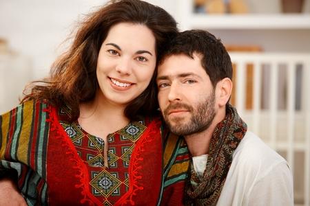 Gelukkig jong paar dat thuis camera bekijkt, het glimlachen.% 00 Stockfoto