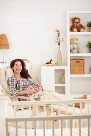 Zwangere vrouw die in leunstoel rust die thuis camera het glimlachen bekijkt.% 00