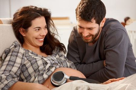 Happy pregnant woman resting in armchair at home husband holding earphones to naked belly.