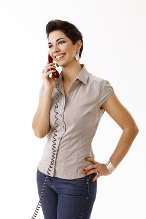 Gelukkige jonge vrouw aan de telefoon in toevallig geïsoleerd op wit. Stockfoto