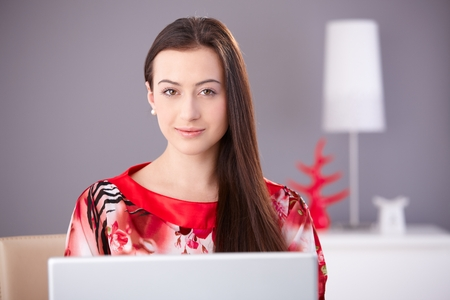 Beautiful young woman in red kimono working on laptop computer, looking at camera, smiling. Stockfoto