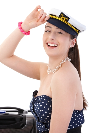Portrait of happy young woman with suitcase in summer dress and sailor hat, looking at camera, laughing. Isolated on white.