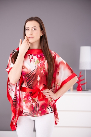 Beautiful young woman posing in red kimono, looking away, touching face, hand on hip.