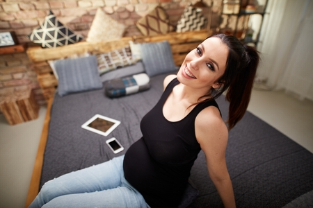 Happy pregnant woman sitting on bed at home smiling, relaxing. Stockfoto