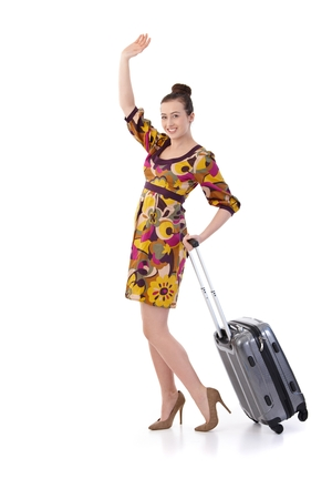 Young woman traveling to vacation with suitcase  in summer dress, posing, looking at camera, smiling. Isolated on white.