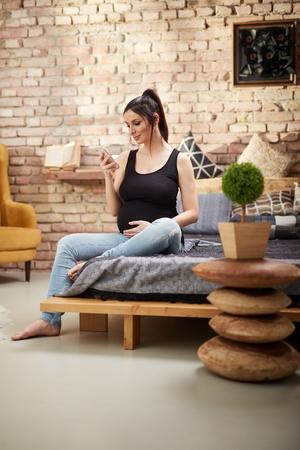 Happy pregnant woman sitting at home smiling, relaxing using mobile phone. Standard-Bild - 125784998