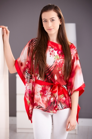 Beautiful young woman standing in red kimono, looking at camera, smiling. Stockfoto