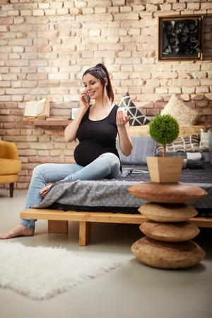 Happy pregnant woman sitting at home smiling, relaxing talking on phone.