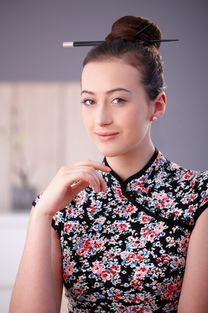 Portrait of beautiful young woman in asian outfit, looking at camera, smiling. Stockfoto