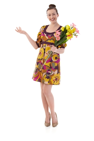 Happy young woman posing in summer dress, holding a bouquet of flowers, looking at camera, smiling. Isolated on white. Stockfoto