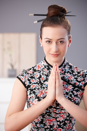 Portrait of beautiful young woman in asian outfit, hands clasped, praying, looking at camera, smiling.