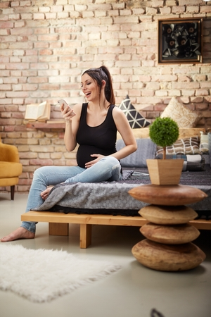 Happy pregnant woman sitting at home smiling, relaxing using mobile phone. Stockfoto