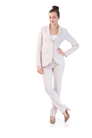 Happy young businesswoman posing in elegant clothes, looking at camera, smiling. Isolated on white.